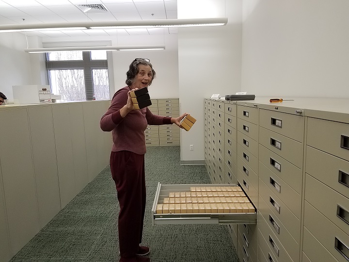 Frances Hager, Acquisitions, Serials, and Government Documents librarian, holds up microfilm being consolidated into fewer cabinets.