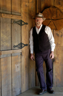 Photo of Dave Smith, a handsome older gentleman in white shirt, dark vest, dark pants, and brown hat. He has a white beard and mustache of moderate length