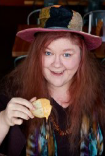 A picture of Kat Robinson, a friendly-looking hippie lady with long red hair and a floppy hat. She appears to be holding a chip covered in cheese dip.