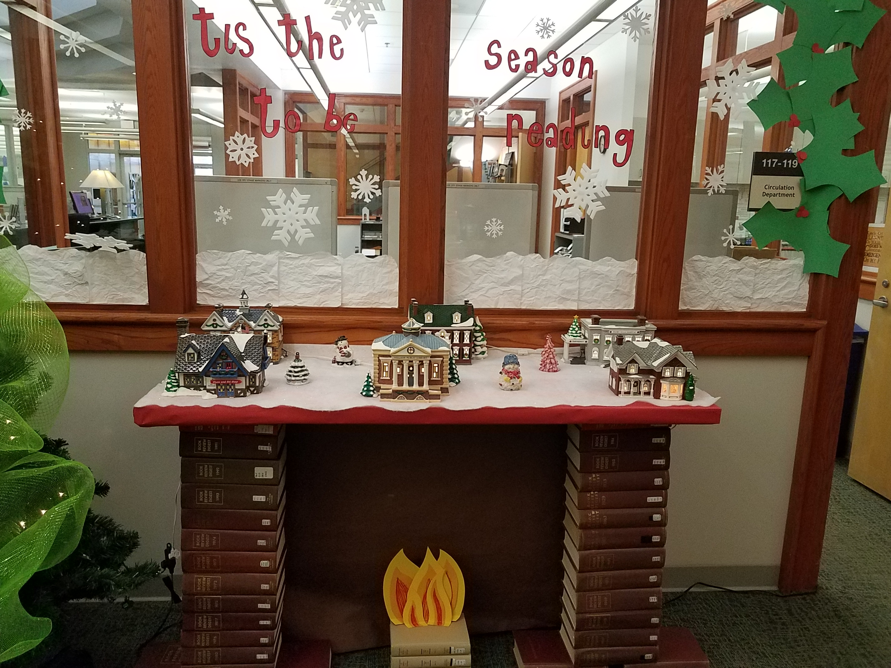 A fake fireplace created out of books with a little Christmas village on top.
